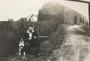 Derek Clemenson at Shakerley Old Hall, c.1940/50s The building rendered in white in the background is the Hall. To the right is the old barn with its multiple bays. (Source: Wigan Archives and Leigh Local Studies)